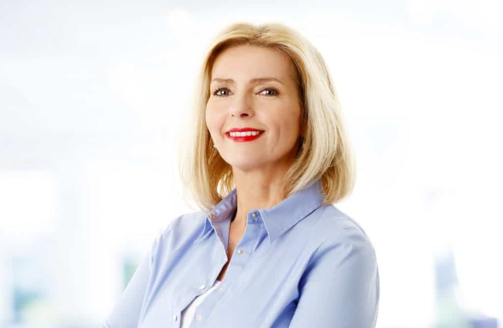 Close-up image of attractive senior woman standing at room while looking at camera and smiling.