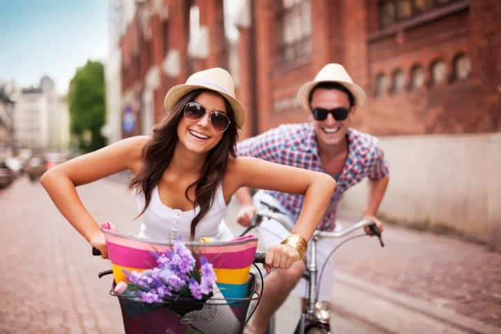 Happy couple cycling in the city